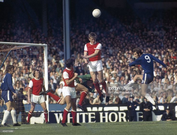 29th August 1971. Arsenal defender John Roberts heads the ball away in front of Chelsea striker Peter Osgood during the derby match at Stamford Bridge in London