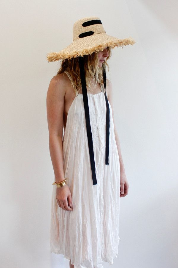 A large brimmed hat with a raffia edge and a black rayon ribbon chin strap. Handmade in Brooklyn, NYC. Size medium.