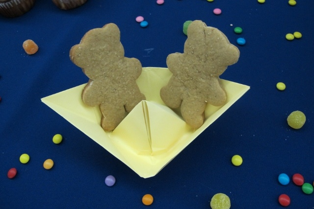 barquinhos de papel serviam de pratinhos para biscoitos em forma de ursinho. jujubas e m`s na mesa.