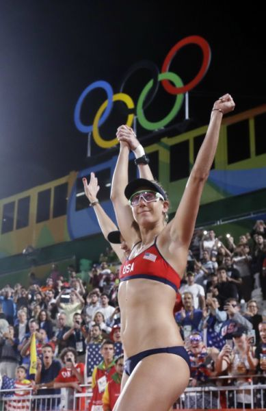 United States' April Ross, right, and Kerri Walsh Jennings enter the arena before a match against China during a women's beach volleyball match at the 2016 Summer Olympics in Rio de Janeiro, Brazil, Tuesday, Aug. 9, 2016. (AP Photo/Marcio Jose Sanchez)