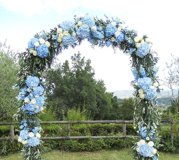 Olive branches and blue hydrangeas wedding arch | Wedding in Borgo Corsignano Tuscany
