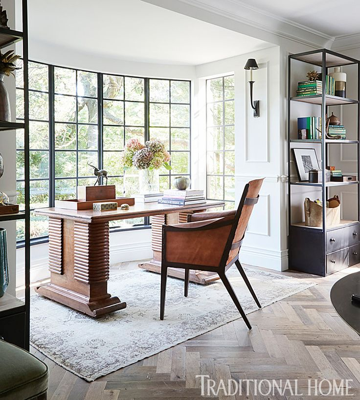 A bright window bay is home to bookshelves and a vintage desk. - Photo: Werner Straube / Design: Summer Thornton