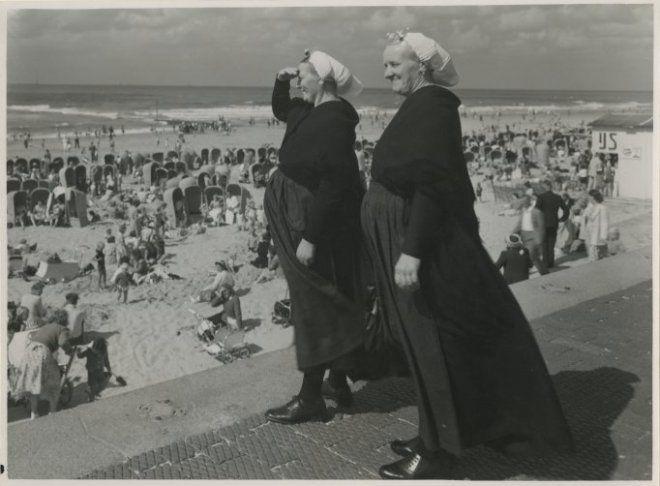 Twee Scheveningse vrouwen kijken uit over strand en zee. 1956 JG van Agtmaal #ZuidHolland #Scheveningen
