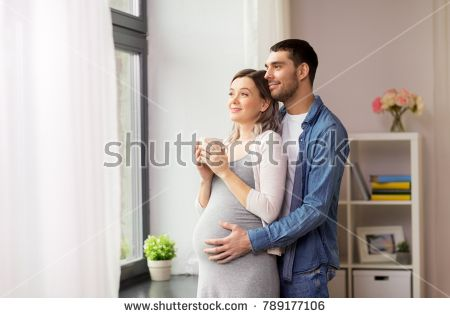 pregnancy and people concept - happy man hugging his pregnant wife standing at window at home
