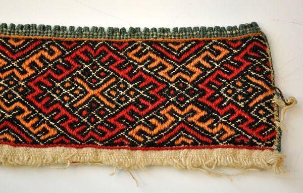 Kvarde Fra protokollen: Smöig, sydd av uldgarn, mæander-ruter i rødt og gult. Gult kors i midten, grønne tagger. Halskvarde til kvinneskjorte fra Øst-Telemark.