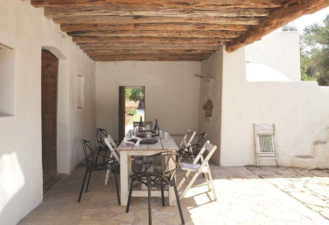 Dehors, tables et chaises en bois et corbeille à raisin Sluiz. Jarres à chaux anciennes.La sabine est le bois roi dans la vie paysanne ibicenca. Sous le porche et dans sa pièce attenante, il est omniprésent, des poutres au four à pain refait par Pipo, l'artisan multidisciplinaire. Toutes les autres portes sont en pino tea, restaurées par l'ébéniste Thierry Billaud.