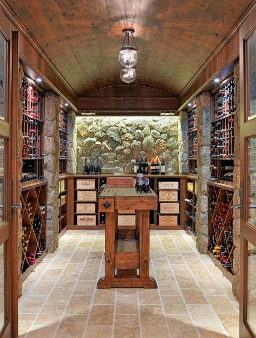 Wine cellar with stone walls and a wooden ceiling | Patrick Ahearn Architect; Built by Sanford Custom Builders; Photography by Richard Mandelkorn