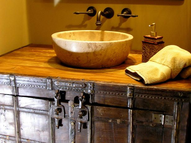 Designer Dan Heldenbrand used a stone bowl sink and a rustic wood-and-iron cabinet to create a Western-inspired theme in this desert home. Oil-rubbed bronze fixtures and a distressed wood countertop complete the look.