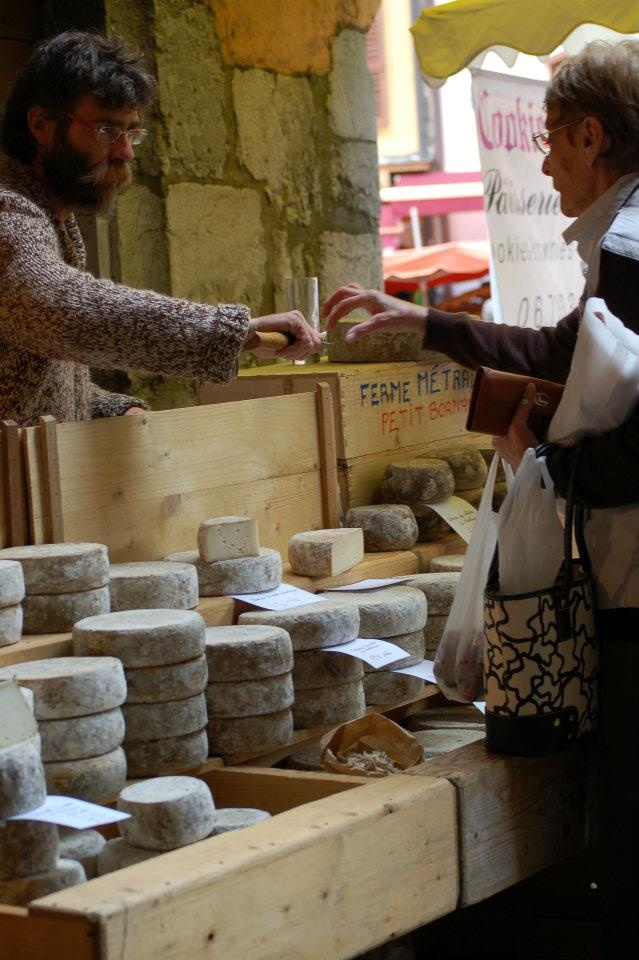 A farmer handing a sample from one of his white wheels of cheese to an early morning patron in Annecy, France.