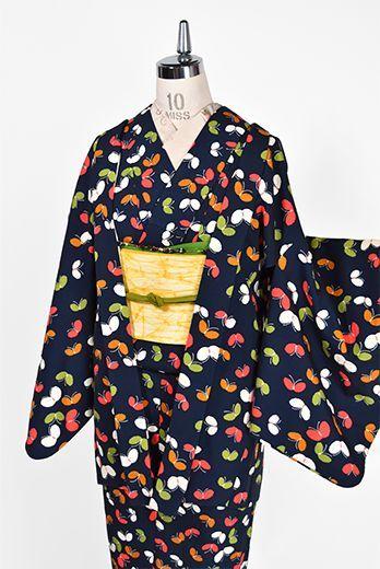 黒に近い濃紺色をベースに、ハーブグリーン、ソレイユオレンジ、ポピーレッド、スノーホワイトなどカラフルな蝶々模様が染め出されたウールのアンサンブル(着物と羽織のセット)です。