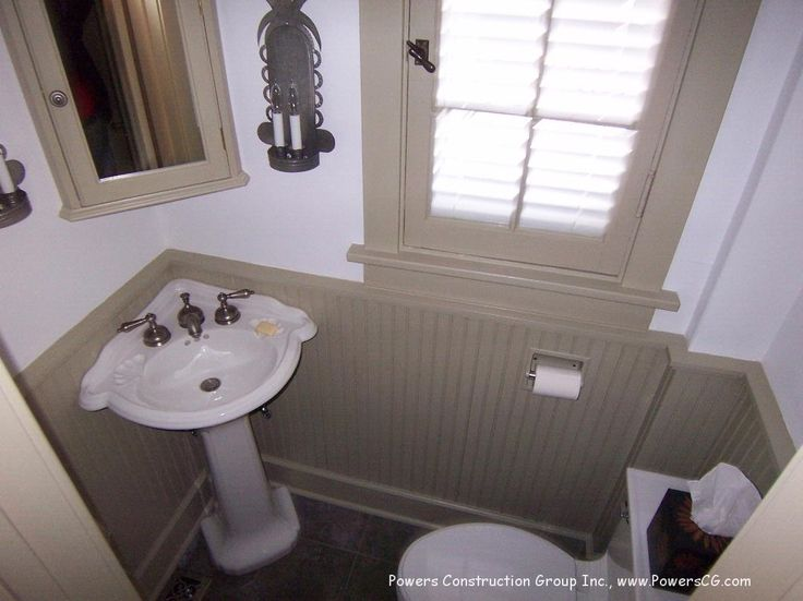 Small powder room with pedestal sink in the corner and beadboard walls. - half bath