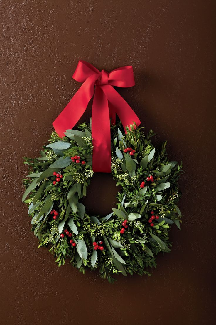 This aromatic boxwood wreath makes for a great Christmas decoration. Its festive red faux berries and a bright red ribbon make this winter door wreath a showpiece for your own front door, above the fireplace, or as a perfect gift anyone will treasure.