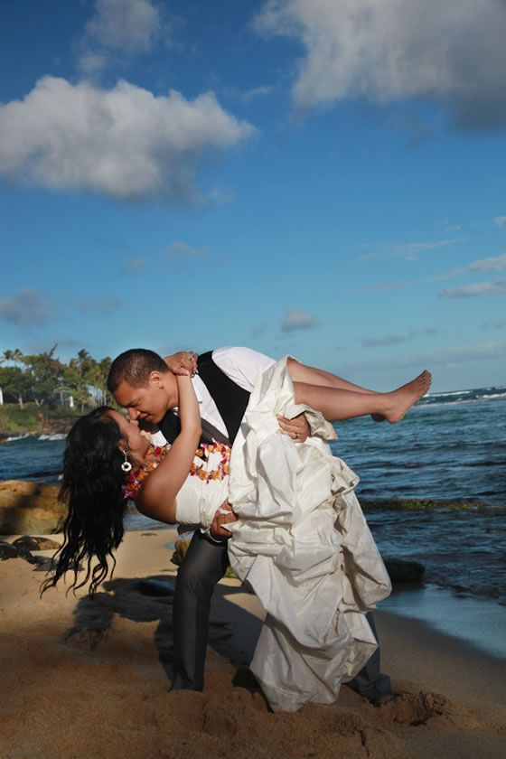 A great beach wedding photo idea! We love that the bride is barefoot in the sand. Image by LucieXYZ Photography.