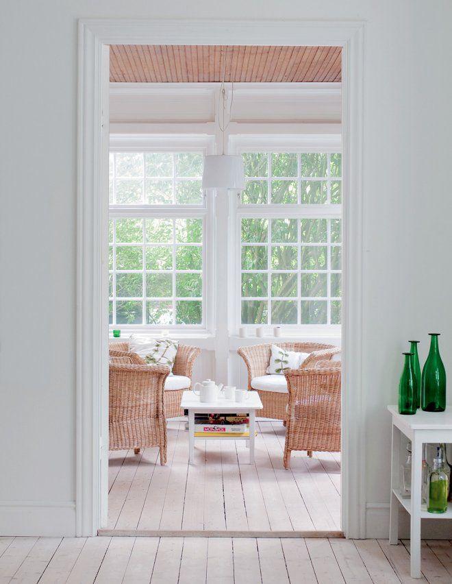 Jardin d'hiver aménagé d'une table  blanche. Au sol, un parquet clair en bois blanchi