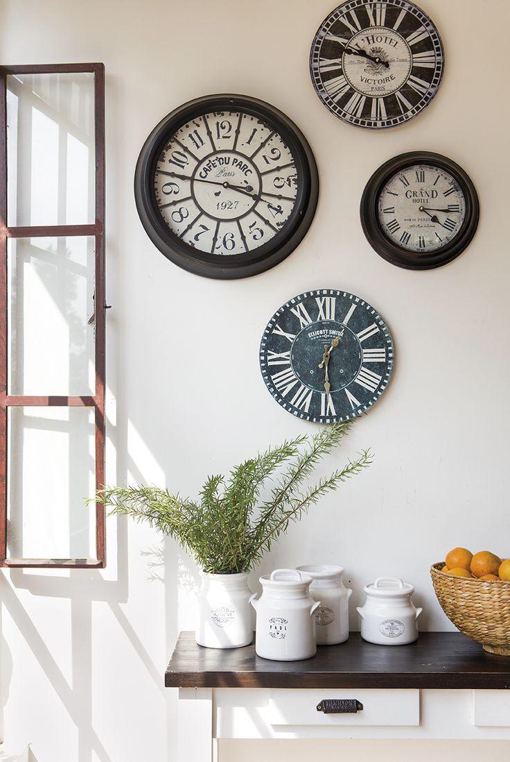 00409382. Cuatro relojes marcando de diferentes colores y estilos sobre una pared blanca_00409382