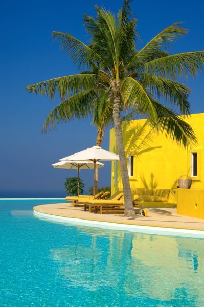 vibrant colors beach estate. bright yellow painted house with white outdoor umbrellas, palm trees, bright blue sky and turquoise water. heaven.