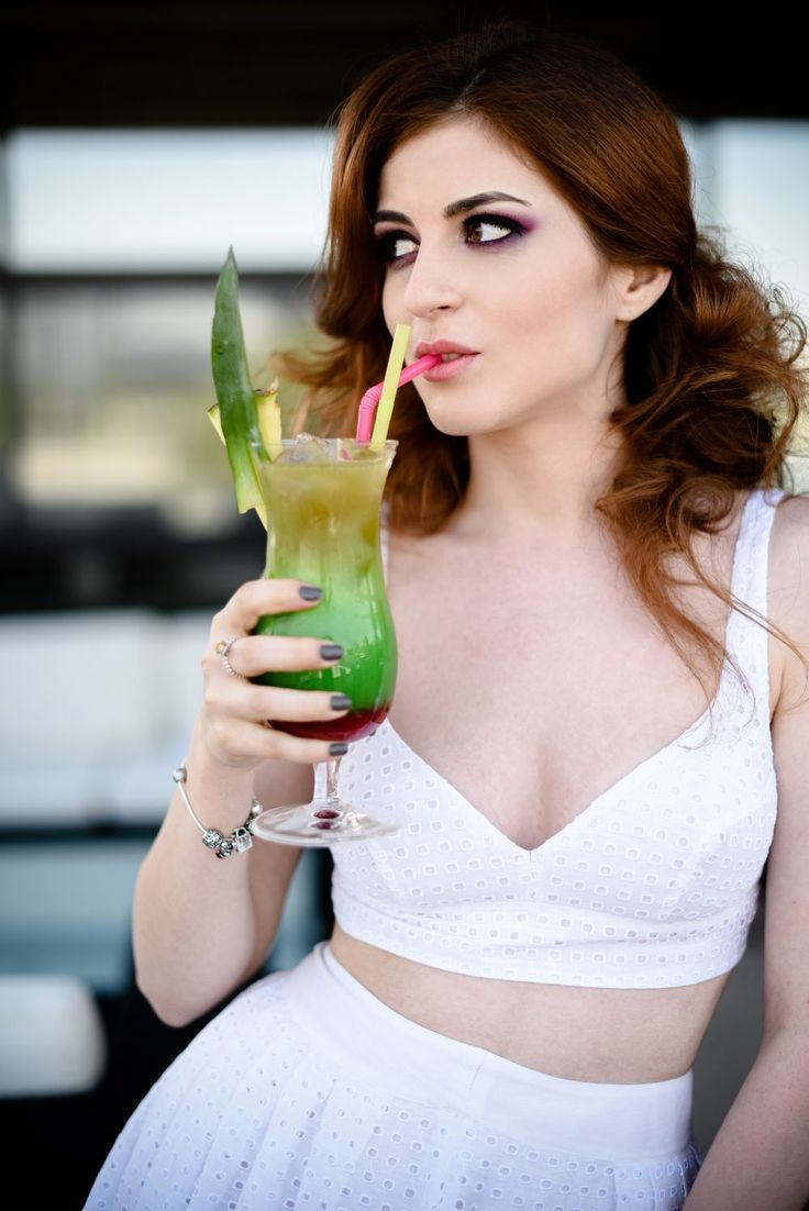 Cocktail at the pool, wearing a white crop top and skirt from Madame Aime Paris