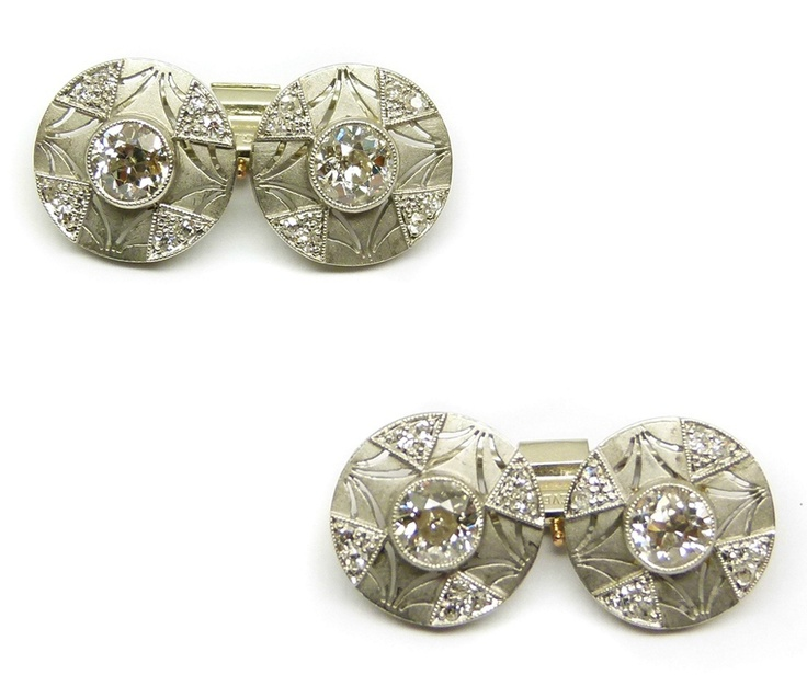 Pair of round panel diamond and platinum cufflinks,   each centred by a round brilliant cut diamond in raised collet, to a pierced frosted platinum panel with four diamond cluster wedge motifs, bar connections