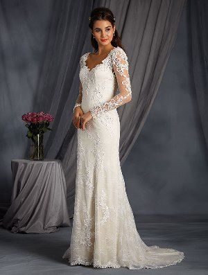 Timeless gown of net and all over lace layered over charmeuse that features a dramatic low sheer back neckline, full length sheer lace sleeves and a soft fit and flare silhouette.  The sweetheart neckline and sleeves have been delicately crystal beaded throughout and the softly flared skirt finishes with a chapel length train trimmed in matching applique.  Also available with Straps as Style 2547  Sizes: 0 to 26W