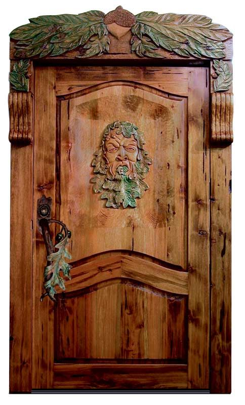 """Inspired by myths world wide, this door has the """"Green Man"""" hand carved onto the outward facing side of the door. Oak leaves and acorns surround him and adorn the frame with the hand forged handle accenting the colors and foliage as well."""