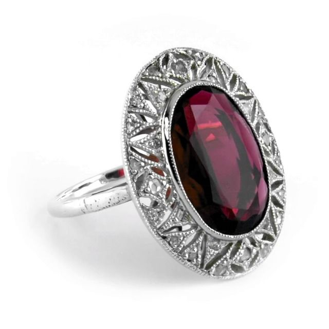 A remarkable and mesmerizing oval tourmaline is bezel set and made more beautiful by a glittering diamond halo in this Edwardian-era ring. Twenty-eight accent diamonds, set with exquisite geometric detailing surround the four carat center gem, creating a lavish and luxurious masterpiece (approx. 0.23 total carat weight).