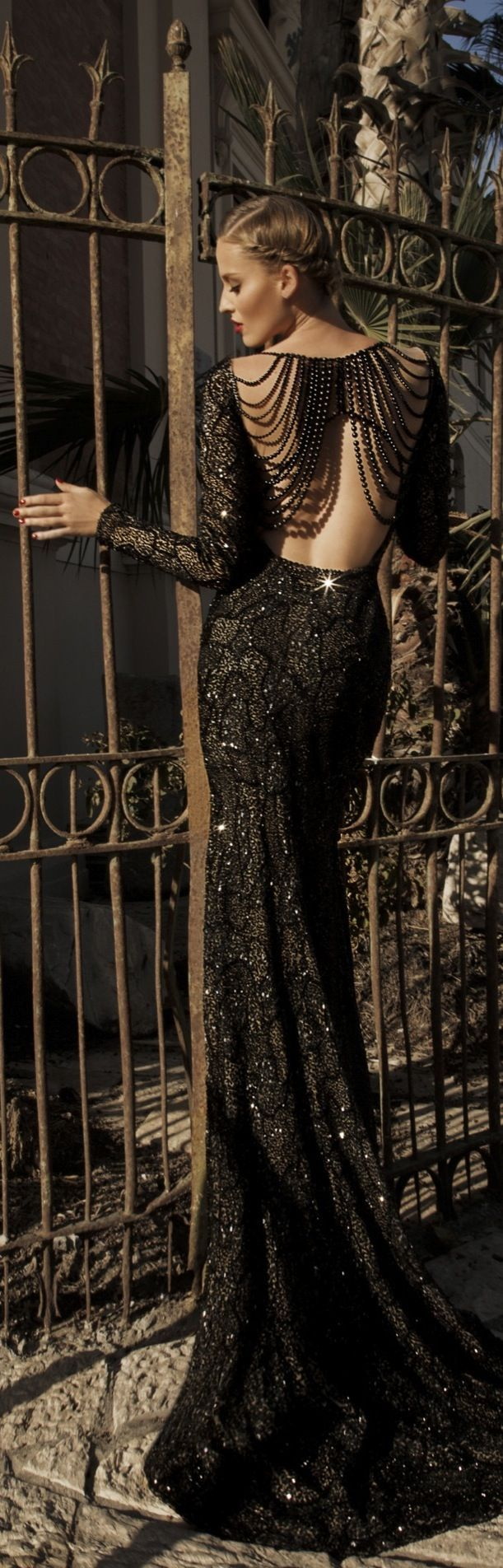 Jupiter: Entirely embroidered in jet-black glass beads that layer over sheer net with draping of black pearls. Necklaces covering the entire back with a very high slit on the front skirt- Galia Lahav