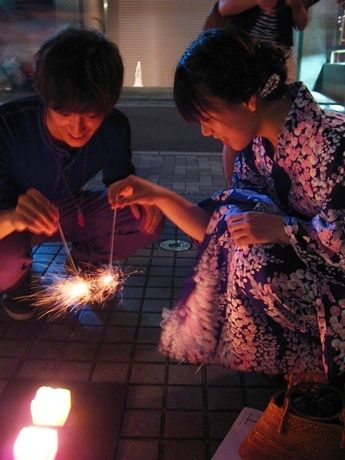 Playing 線香花火 (senkō hanabi), a sparkler fireworks which is one of summer features in Japan.  ☆線香 (senkō or osenkō) literally means 'incense stick' burned at the Buddhist temples, graves, and family alters when praying.