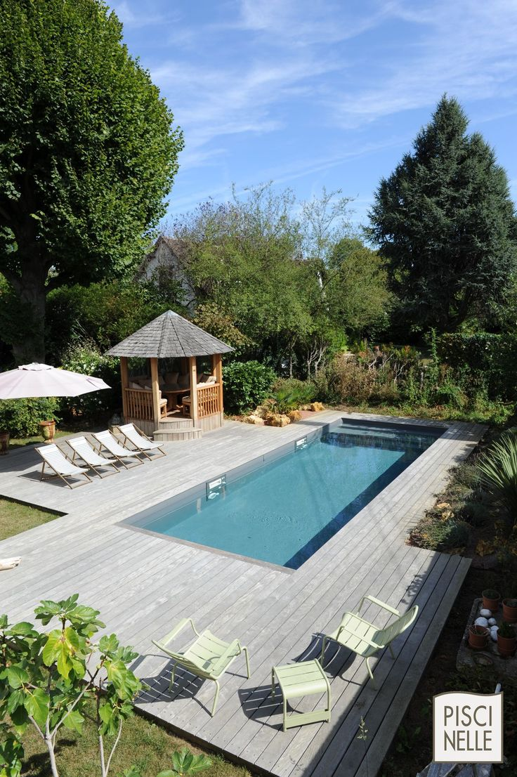 Piscine traditionnelle dans un pavillon de région parisienne. La piscine dispose d'une structure en aluminium et est équipée d'un liner gris ardoise qui lui confère un aspect de bassin intégré à l'ensemble.