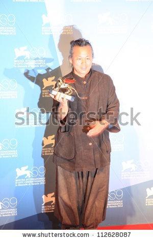 VENICE - SEPTEMBER 8: Kim Ki-duk shows the Golden Lion to photographers at 69th Venice Film Festival on September 8, 2012 in Venice, Italy. - stock photo