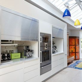 Contemporary Kitchen by Johnny Grey Studios - interesting shutters to hide everything away