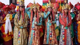 Vier buddhistische Mönche in festlichen, reich verzierten Trachten. | Bildquelle: dpa