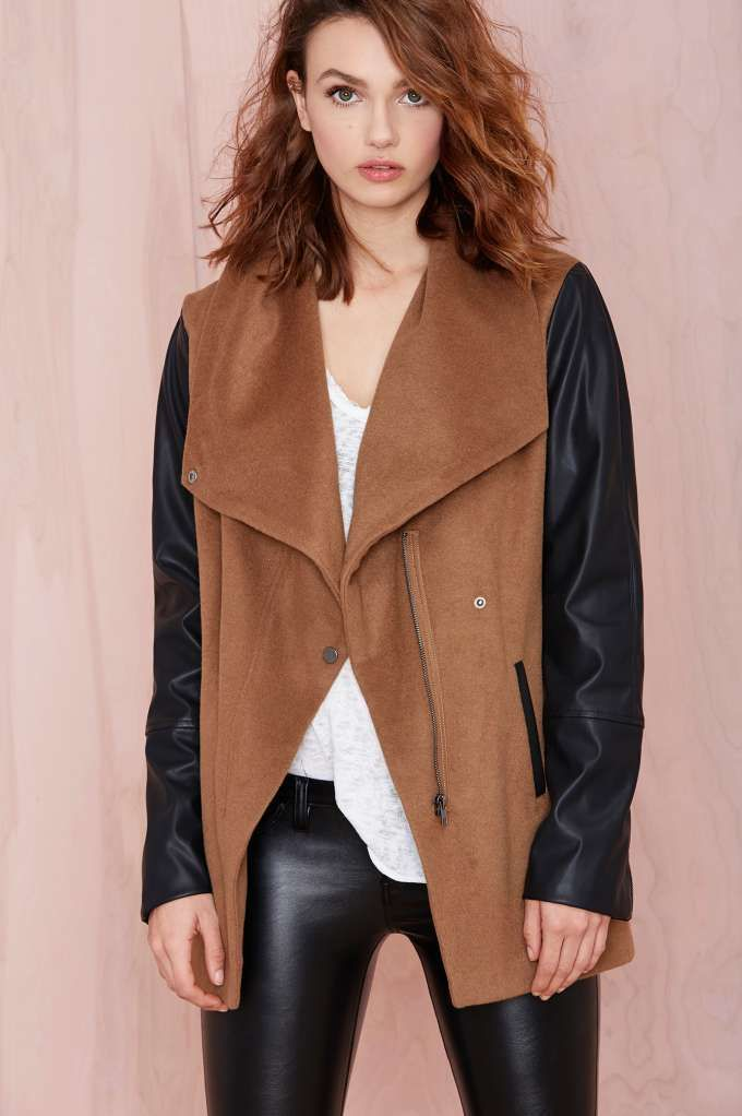 Ready to fend off some paparazzi? The High Profile Coat has a camel shell with tall drape collar, asymmetrical snap closure, faux leather sleeves and pocket trim, zip closure at front and sleeves, and uneven hemline.