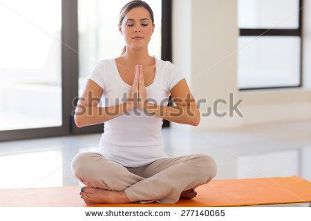 peaceful young woman doing meditation at home