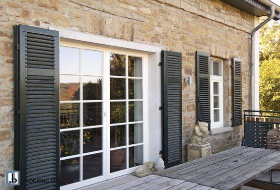 Die Sprossenfenster werden von funktionalen Fensterläden eingerahmt.