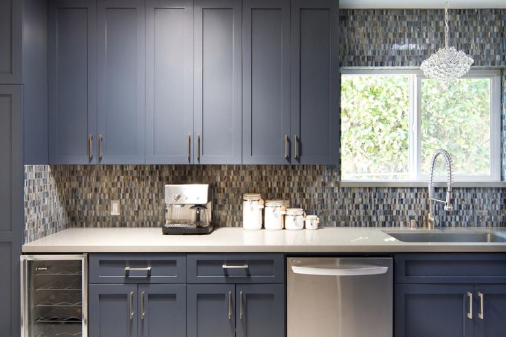 Custom blue Shaker cabinets and the pental quartz backsplash give this midcentury modern kitchen visual life. Counters and appliances are kept sleek and fuss-free, with plenty of room for modern conveniences like an espresso machine and wine refrigerator.