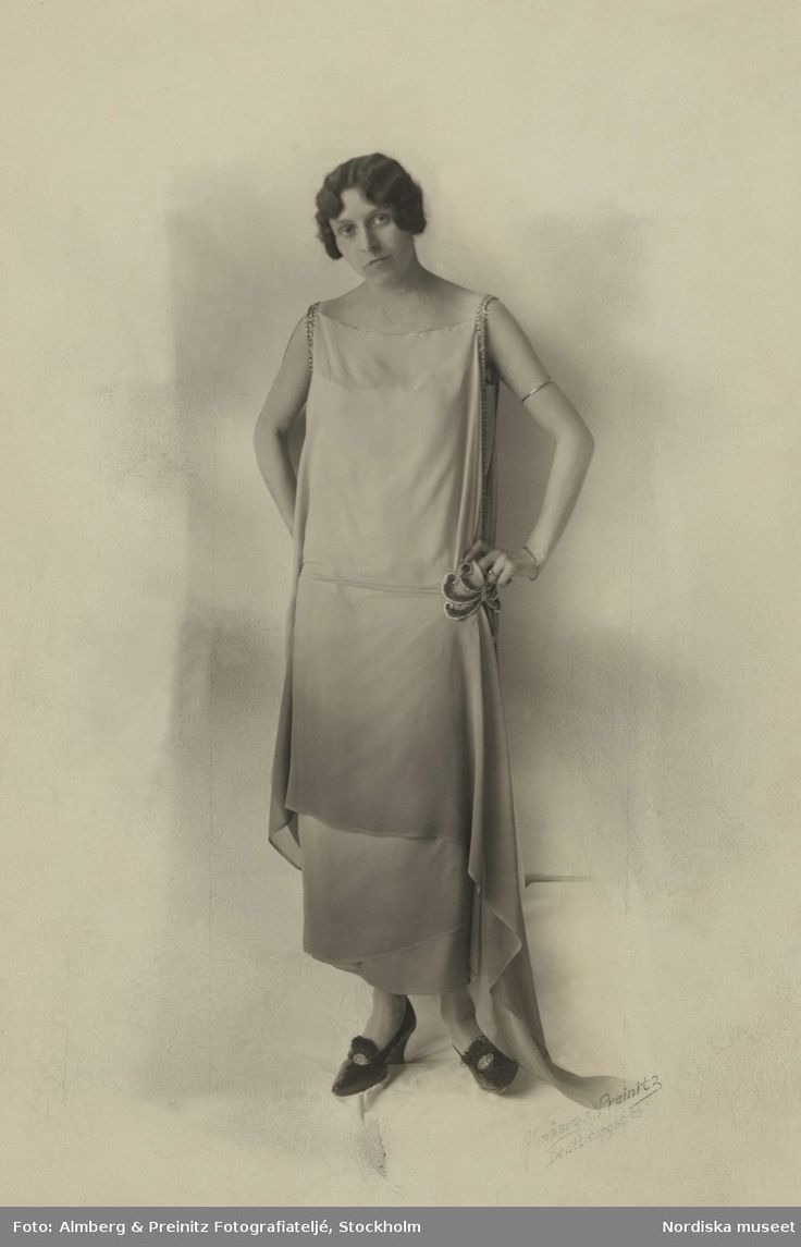 Modell poserar i en ljus aftonklänning, ca 1920-1929. Foto: Almberg & Preinitz Fotografiateljé, Stockholm, för Nordiska Kompaniet.