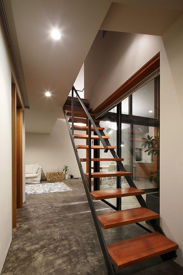 玄関ホールの階段はシンプル、ミニマムにして奥の中庭への抜けを邪魔しないように。