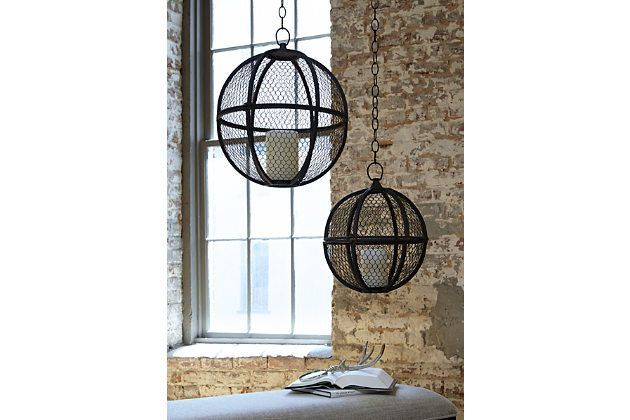 Two sphere shaped hanging candle holders shown against a stone wall and window.
