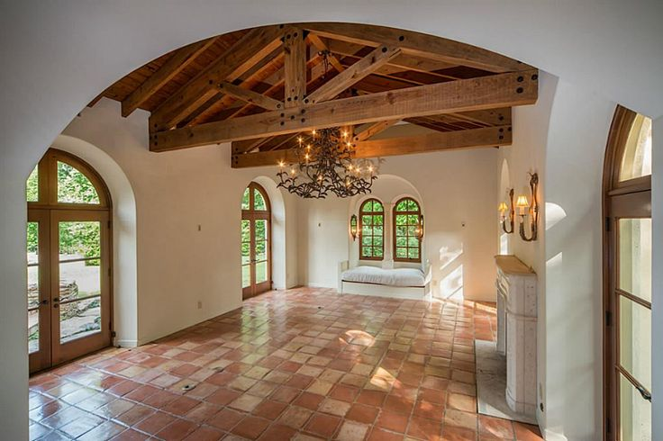 Gorgeous Spanish inspired room with wood beams, terra cotta floors and stucco walls.