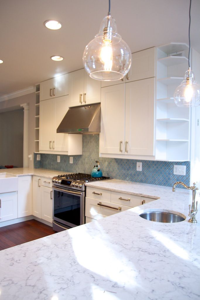 White cabinets, polished nickel pendants with Edison bulbs, second bar faucet to complement bridge faucet over farmhouse sink, and Moroccan backsplash tile