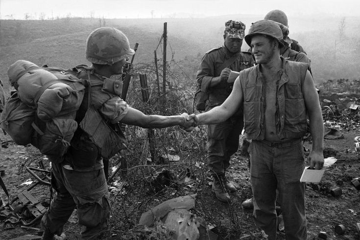 Pfc. Juan Fordona of Puerto Rico, a First Cavalry Division trooper, shakes hands with U.S. Marine Cpl. James Hellebuick over barbed wire at the perimeter of the Marine base at Khe Sanh, South Vietnam, early April 1968. The meeting marked the first overland link-up between troops of the 1st Cavalry and the encircled Marine garrison at Khe Sanh.