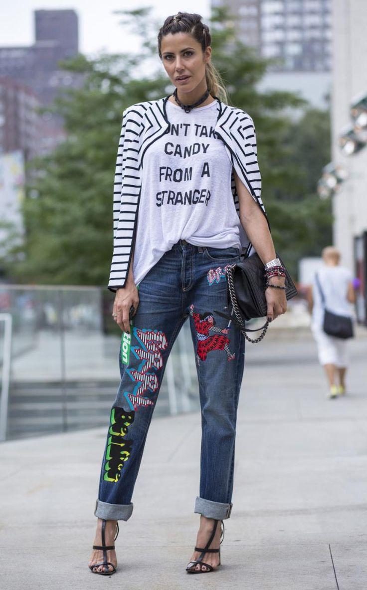 Look de street style super estiloso: calça jeans com bordados, camiseta com frase, casaquinho listrado e salto alto.