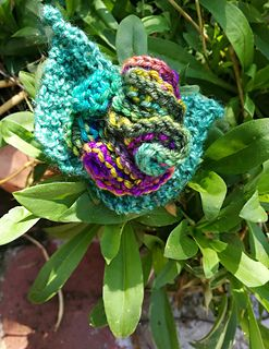 Brooch is knitted in small amounts of 4 ply yarn. There are two knitted leaves and a lovely ruffled flower attached to a button on a brooch back . All parts are knitted separately and sewn together.