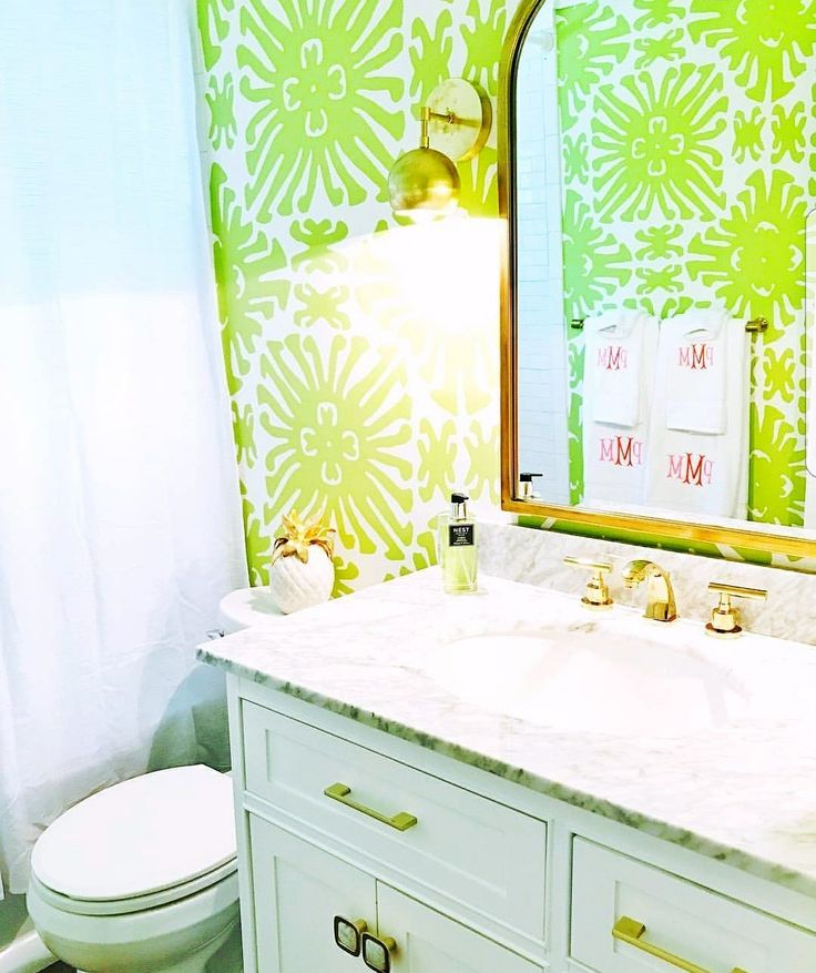 Green tropical wallpaper, pink embroidered towels, marble countertops, brass mirror, and all brass Loa wall sconces by Sazerac Stitches.