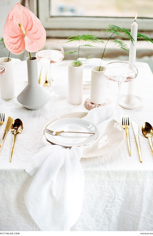 Modern, clean table setting with white linen table cloth, pink flowers and gold cutlery
