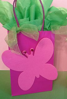 Glue a large foam shaped butterfly to a solid color gift bag. Tie a ribbon on the handle and finish with colorful tissue paper. Use them as party bags and as table decorations.