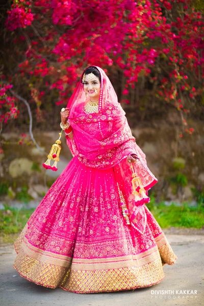 twirling lehenga shot, twirling bride shot, fuchsia lehenga, gold and pink kaleere, gold maagtikka, gota border
