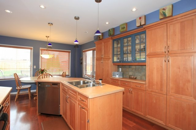 Custom KitchenCraft maple cabinetry with built-in garbage bins, specialty shelving