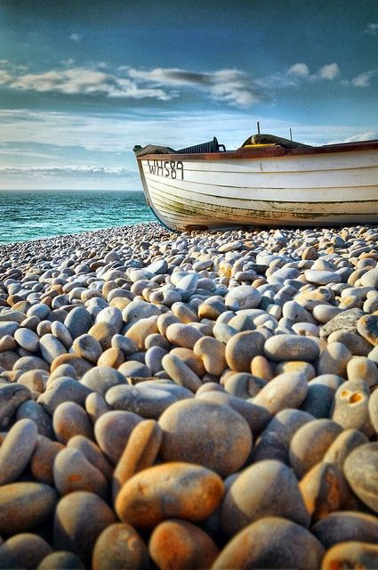 ROCKS ~ Beautiful rounded rocks along the shore for as long as the eye can see.  Beach pebbles & rowing boat