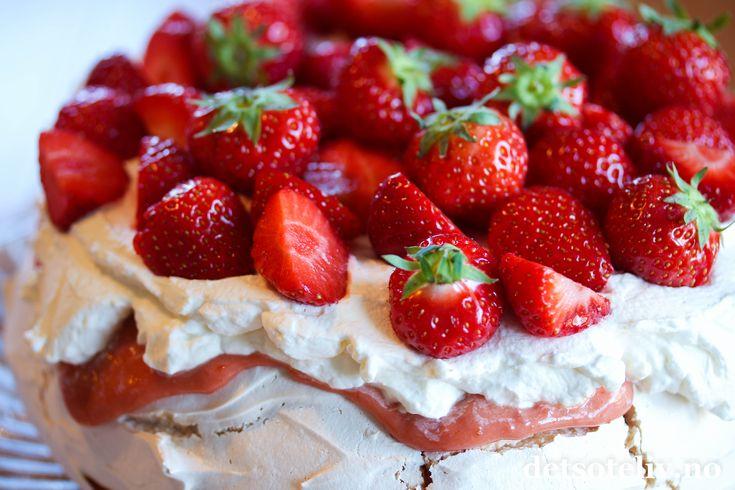 """Her har du en skikkelig deilig sommerkake! En klassisk Pavlova dekkes her med en nydelig """"jordbærcurd"""", som er et fornorsketnavn på engelsk """"Strawberry Curd"""". Dette er en nydeligkrem med smak av sitron og jordbær, som passer perfekt til den deilige marengskaken! På toppen har jeg dekket med pisket krem som er søtet med vaniljesukker og masse, friske jordbær."""